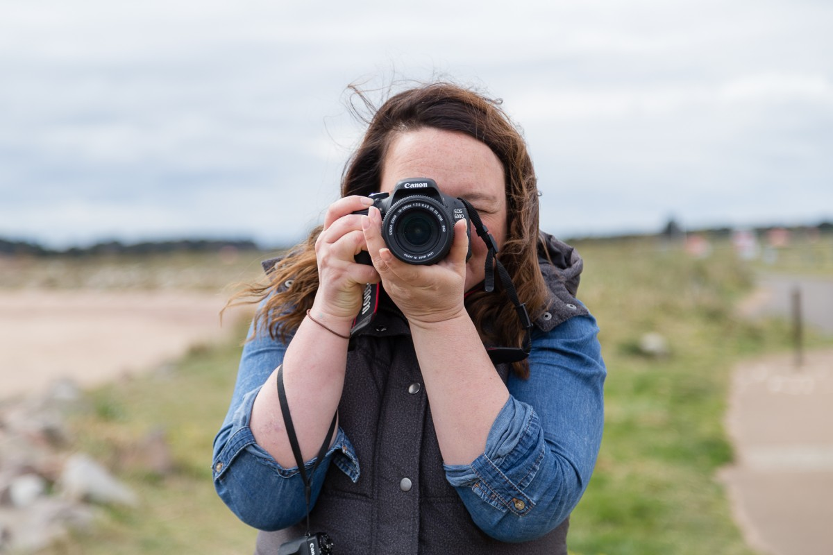 5 ways to improve your business photography VIcky Gunn, Millie's BeachHuts with DSLR camera taking a photograph